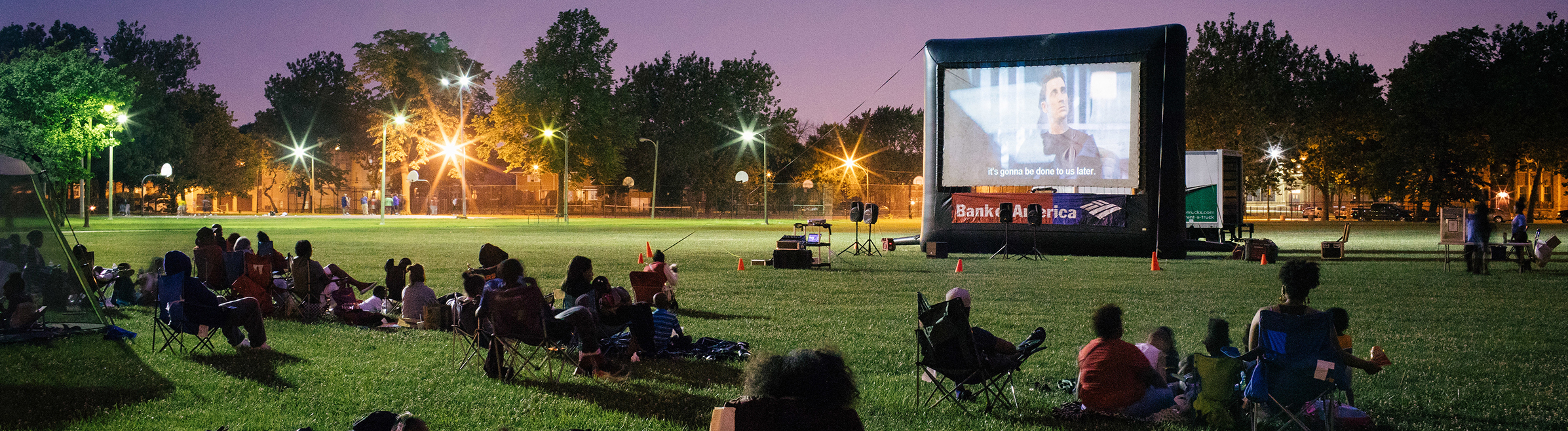 A crowd sits around an outdoor movie screen to watch a movie in the parks.