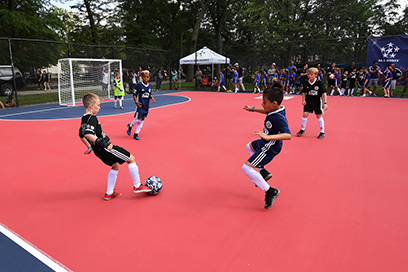 Chicago Fire Soccer Club players enjoy a game on a mini-pitch in a Chicago park.