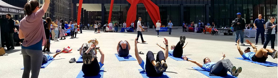 Led by an instructor, a group of people work out at the annual Chicago Moves Day event at Federal Plaza.