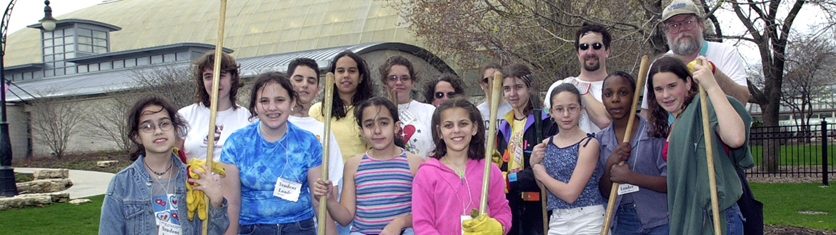 A group gathers for a photo after a day of cleaning up a park in celebration of Earth Day.