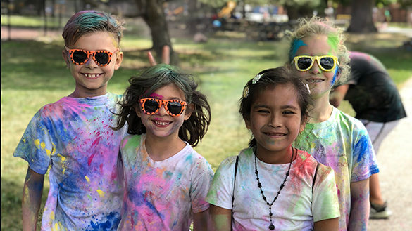 Kids with bright colors over their clothes and hair pose for a photo after a color run as part of the day camp program.