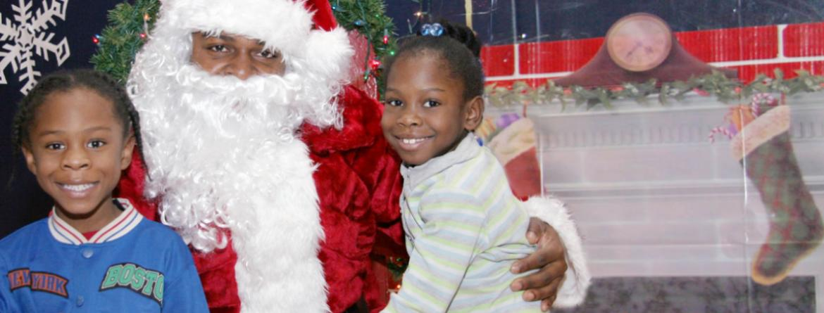 Two girls pose for a photo with Santa at a holiday event in the parks.