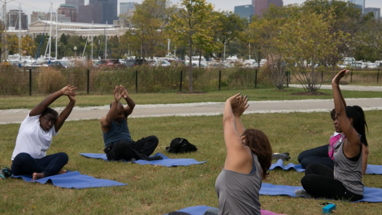Volunteers enjoying a class of yoga on Northerly Island's lawn.