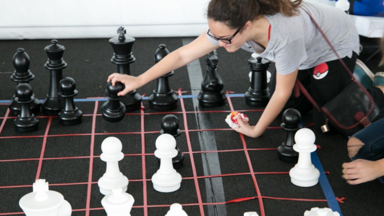 Volunteer enjoying playing life size Chess game.
