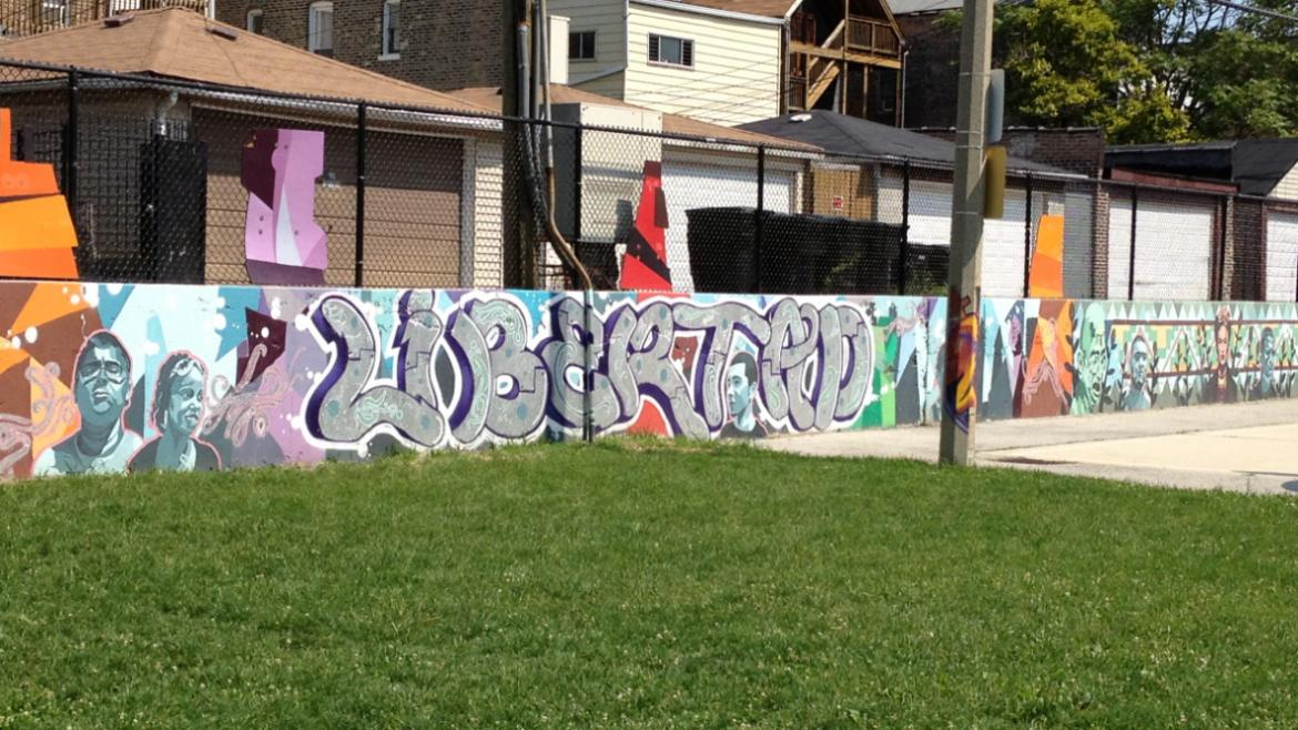 """At the center of the mural, the word libertad (Spanish for """"freedom"""") is painted in larger letters,"""