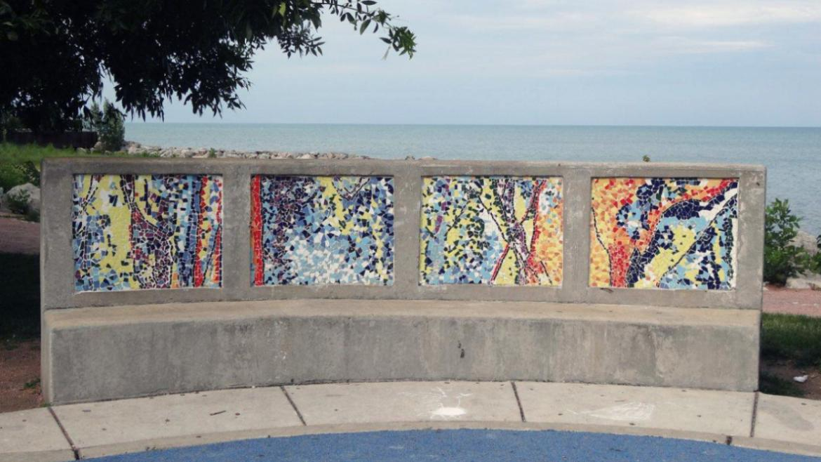 The four panels lining the seat side of the bench have mosaics with abstract imagery in colors
