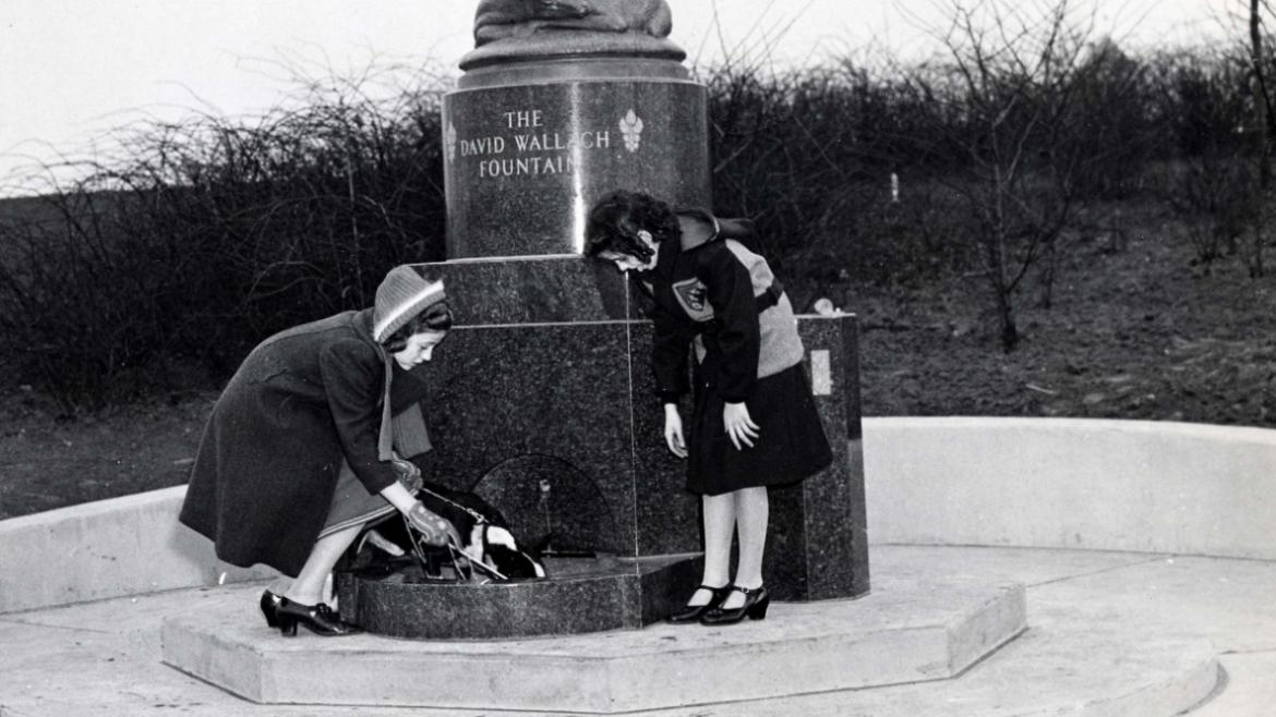 This historic photograph shows two girls with dog drinking from fountain basin, CPD Special Collecti