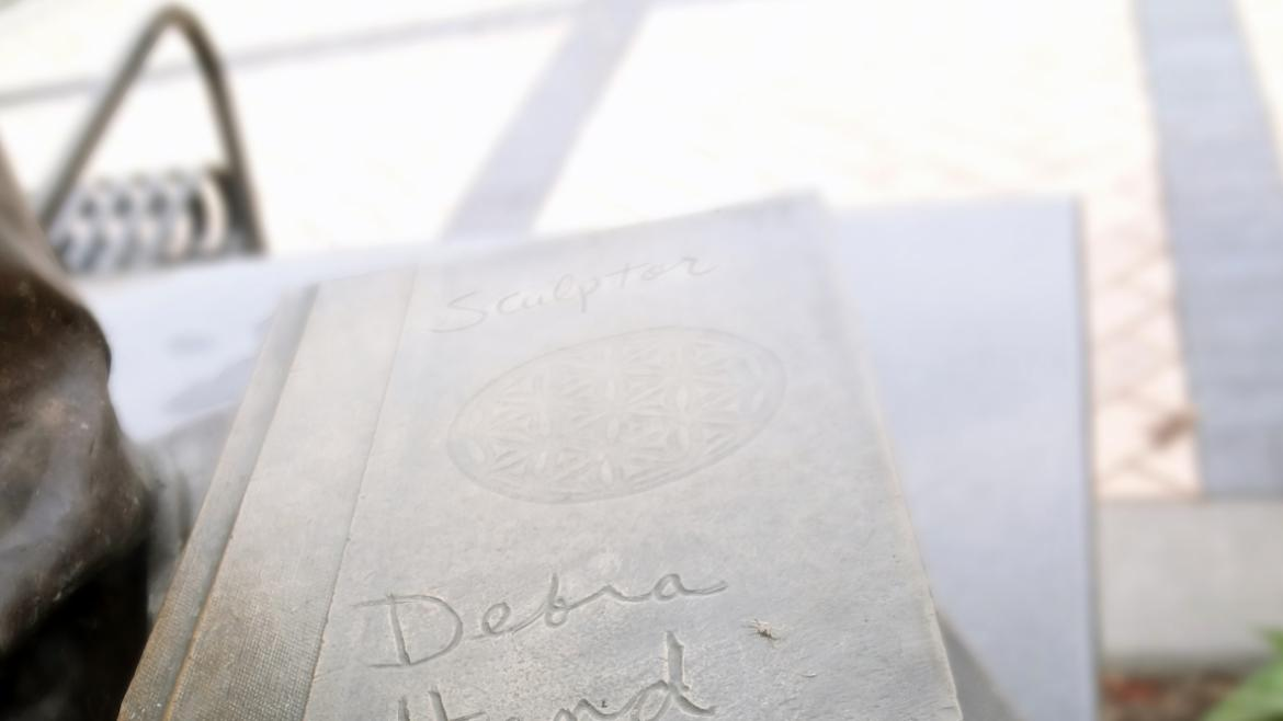 The artist's signature can be found on top of the stack of books near the figurative sculpture, 2015