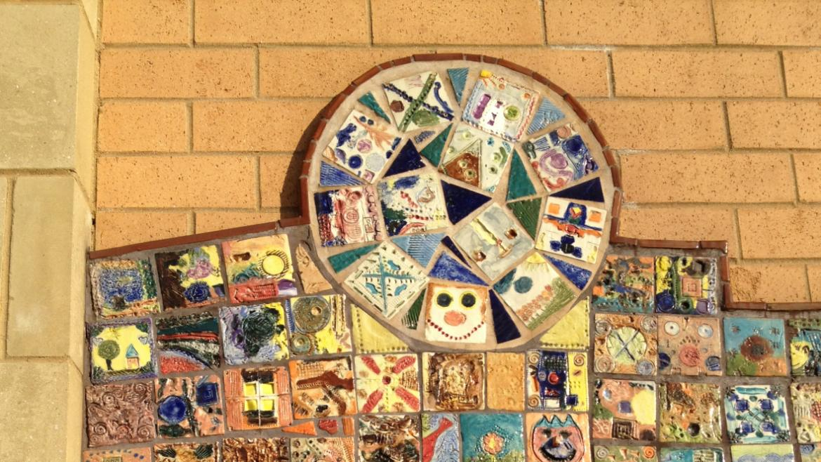 The arrangement of the tiles in the center part of the composition suggests the forms of a child .