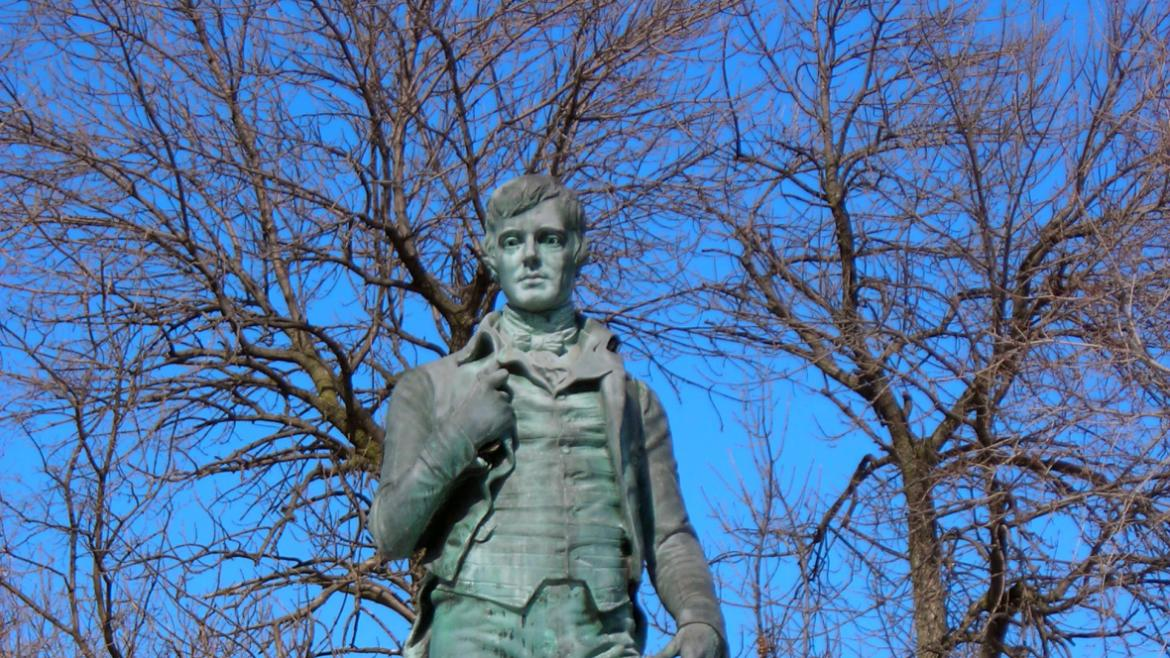 The ten-and-a-half foot high bronze sculpture depicts Robert Burns holding his 1786 book.