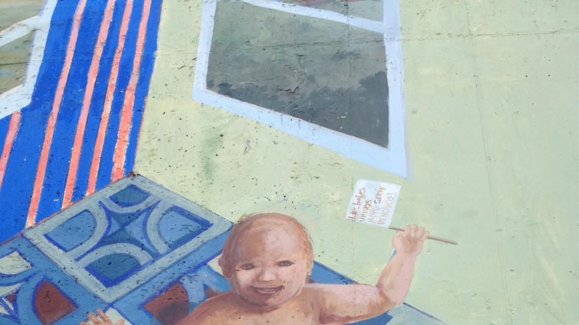 A very large baby is depicted next to a small version of the Gill Park field house.