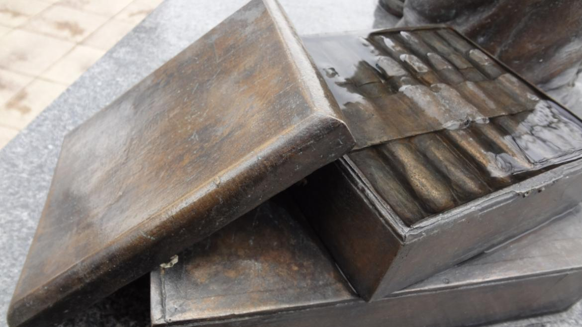 A stack of bronze cigar boxes sits near the feet of the bronze figure of Gompers, 2015.