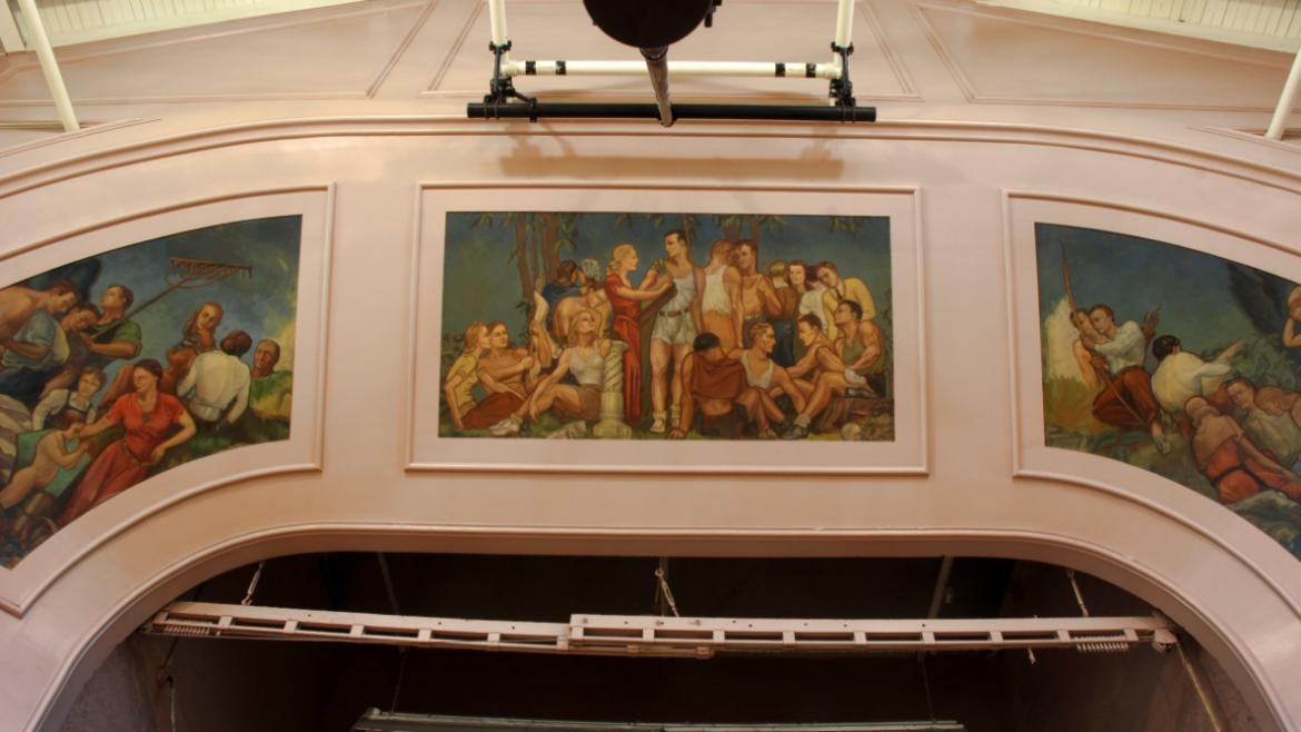 The three panels spanning across the top of the arch depict groups of young men and women  lounging,