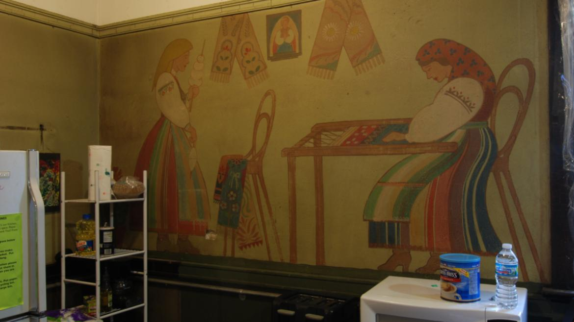Dressed  in traditional Polish clothing, all of the women depicted in the mural are making textiles.