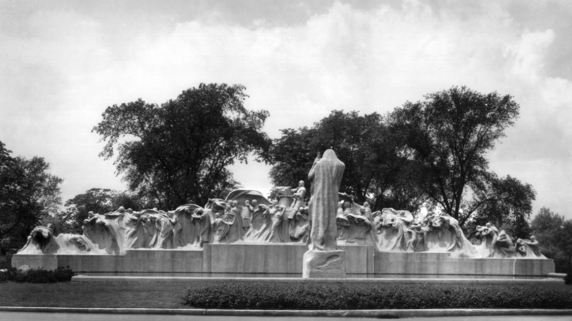 The iconic Fountain of Time includes a cloaked father time figure looking over a wavelike procession