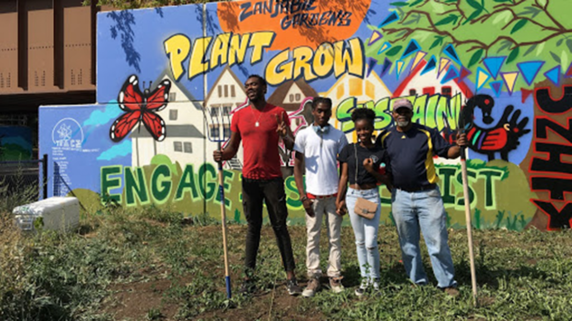 TRACErs Najee Grace and Dartonya Wright in front of 2017 TRACE mural with Zanjabil Gardens owner Kamal Rashid and volunteer.