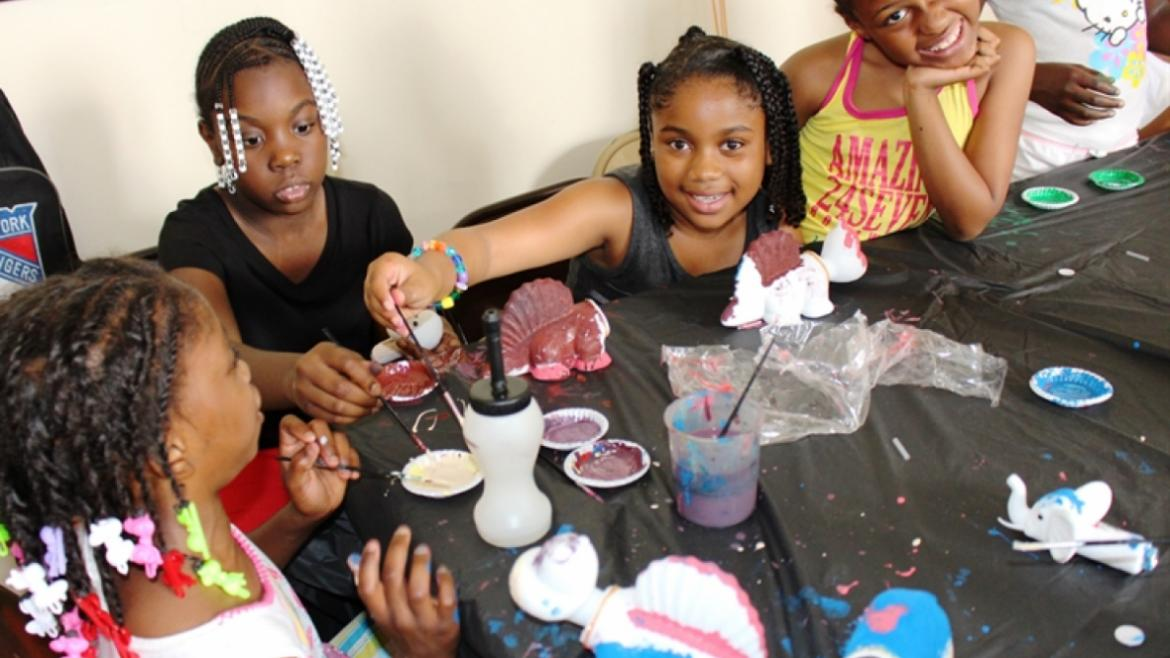 A group of girls smile as they create beautiful artwork at a park camp.