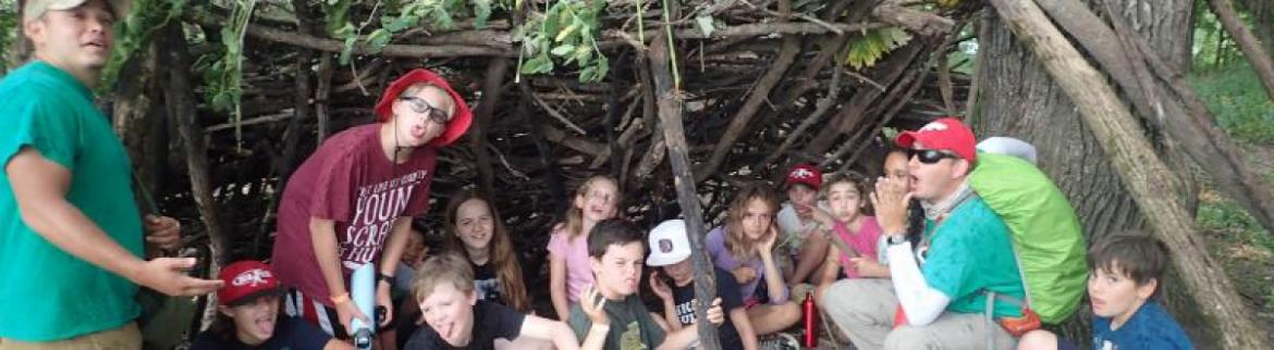 A group gathers for a silly photo under a shelter while hiking together.