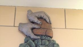 Phil Schuster's sculptural bas relief depicts a pair of hands removing a plant from its pot, 2012.