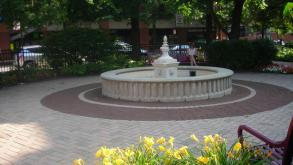The Mid-North Triangle Park Fountain is surrounded by decorative pavers, flower beds, and benches.