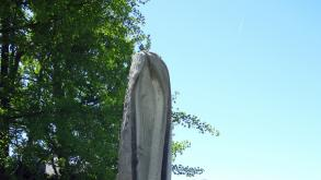 This sculpture has a sinuous vertical form. The rough area of stone on one side is juxtaposed
