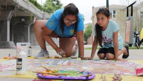 An ArtSeed instructor works on a project with a child in the program.
