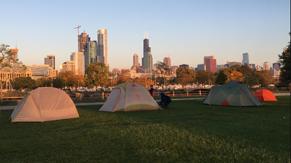 Tents are set up at dusk at Northerly island, with the city skyline in the background.