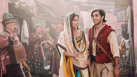 Aladdin and Jasmine, two Middle Eastern young people, walk through a crowded street.