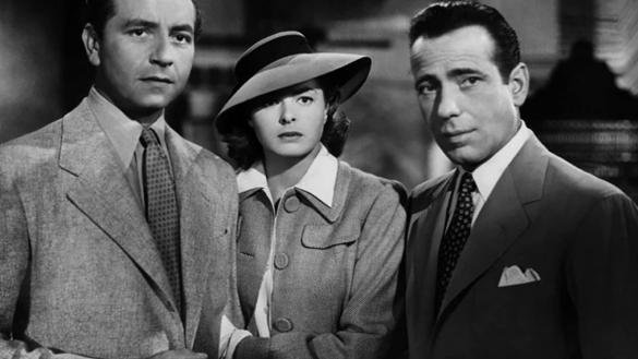 A woman stands with two men, in 1940s overcoats and hats, looking frightened into the distance.