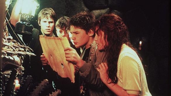 A group of four teens stares intently at a scroll of parchment using a lantern for light.