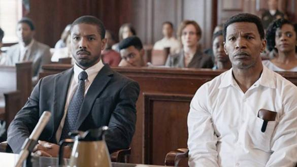 Two African American men, one in a suit one in a white shirt, sit behind a table in a court room.