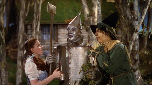 Dorothy, a young woman, stands with a man made of tin and an animated scarecrow.