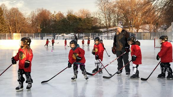 A few young skaters practice hockey skills on the ice with an coach instructing them at a Chicago Blackhawks Hockey clinic.