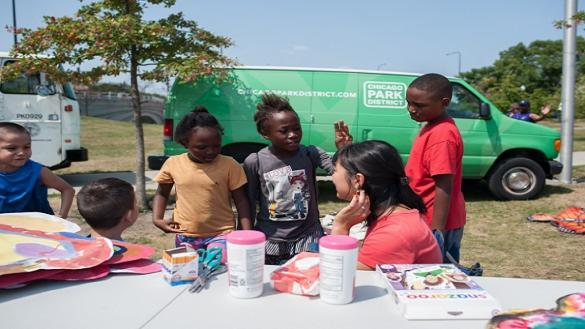 Youth gathered in front of a green ArtSeed van at 31st Street Beach with teaching artist Elaine.
