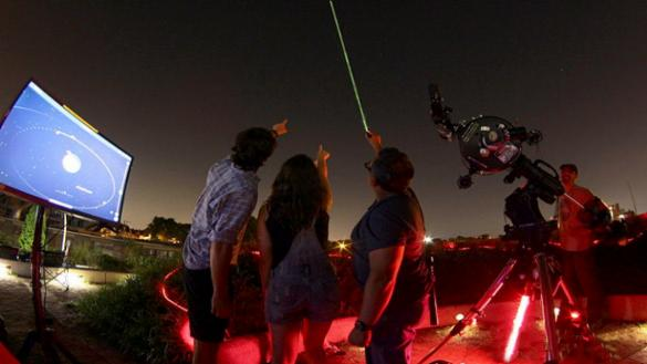 stargazers pointing to the dark sky in front of a telescope and large screen