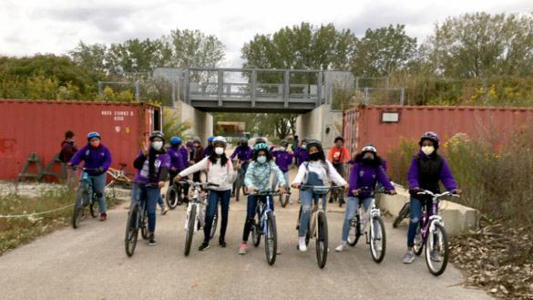 youth emerging from beneath an overpass on bicycles