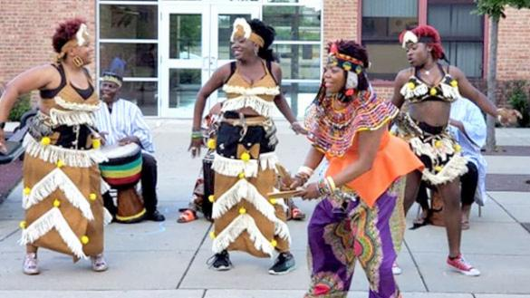 four dancers in West African dress in front of drummer