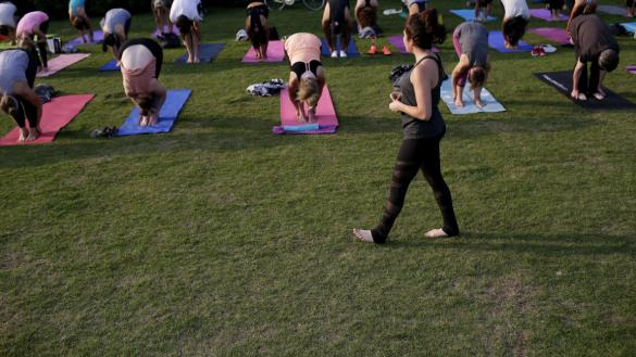 yoga instructor walking in front of rows of patrons stretching on yoga mats