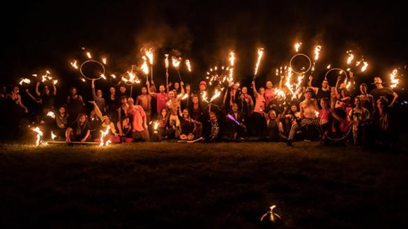 large ensemble of dancers and drummers holding fire hoops and sticks