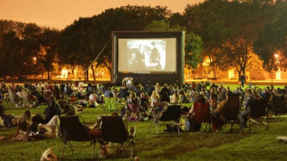 A crowd enjoying a movie in the park