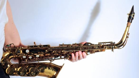 A hand holding a saxophone against a white background.