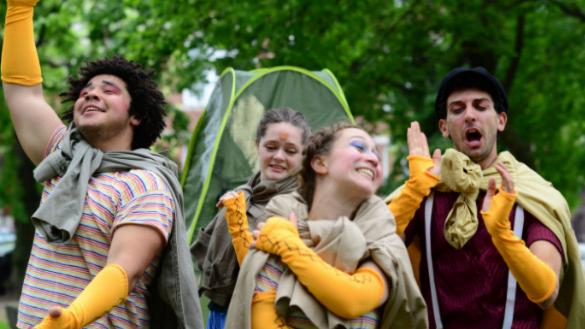 four actors in long yellow gloves, singing and smiling in a park
