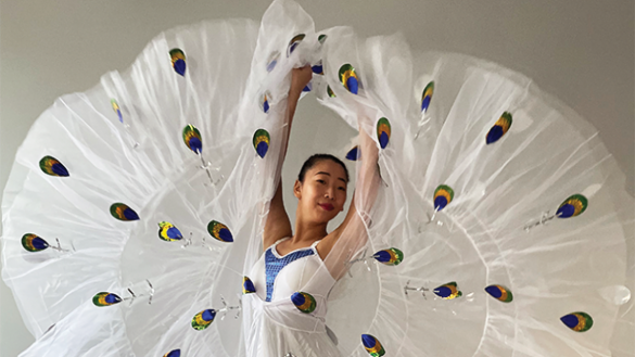 dancer close up with arms stretched above head, wearing a white costume with peacock feathers