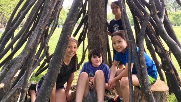 Kids enjoying fun with nature at the Nature Play Space at Welles Park.