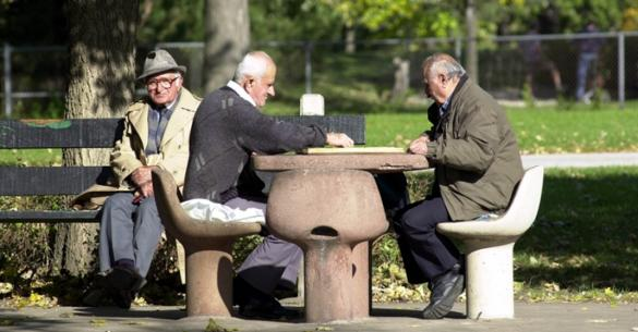 A group of men enjoy a game of chess outside.