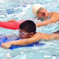 Two children work on swimming techniques in a Learn to Swim class.