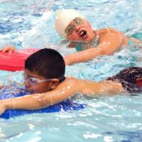 Two children swim across a pool in a Learn to Swim class in the parks.
