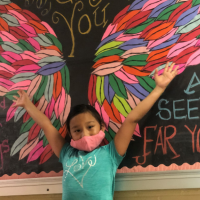 A young girl stands in front of a colorful mural during day camp.