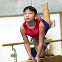 A girl practices on the balance beam in gymnastics class.
