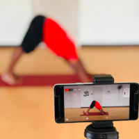 A fitness instructor is filmed during on online yoga class.